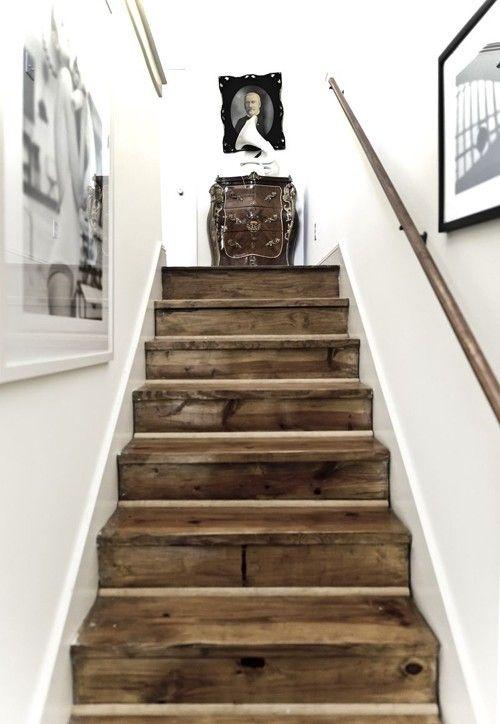 Dark, rustic wood steps between white walls.