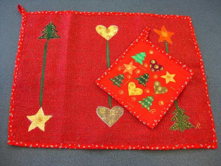 La magia del Natale esordisce in cucina con la tovaglietta e la presina rosse coordinate, con decori di cuori, alberi e stelle.