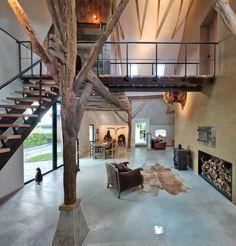 Renovatie woonboerderij met loopbrug naar slaapkamer. monolithisch aangebrachte betonvloer en stalen pui met houten luiken.