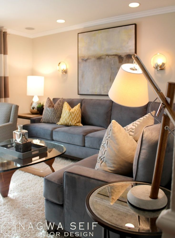 A Warm and Modern Home: Charcoal suede Sofa with pattern accent pillows and glass coffee table.