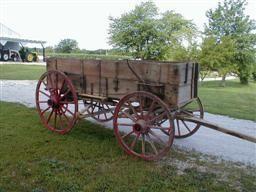 Horse drawn high wheeled wagon.