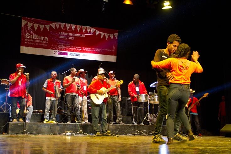 Los asistentes bailan en el escenario