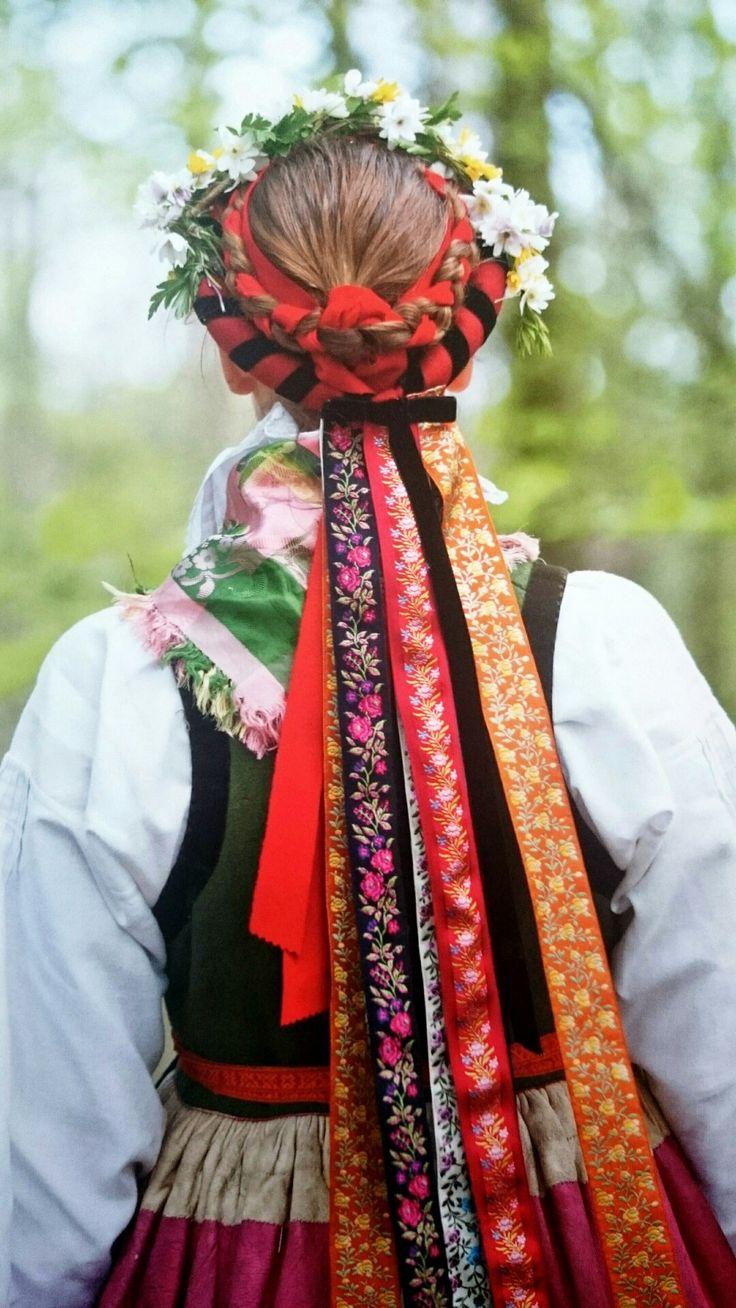 Swedish folklore, Albo Härad, Skåne (Scania). Kvinnans hår är uppsatt i en oppbindning med röda band och utan på det en piglock pyntad med vackra sidenband.