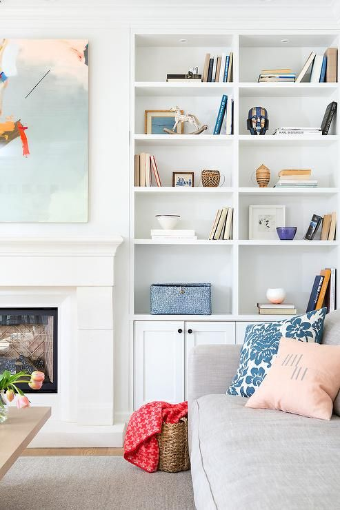 Beautiful living room features a white limestone fireplace tucked under a pink, orange and blue abstract art piece placed next to built in shelves lined with tchotchkes as well as cabinets adorned with bronze knobs.