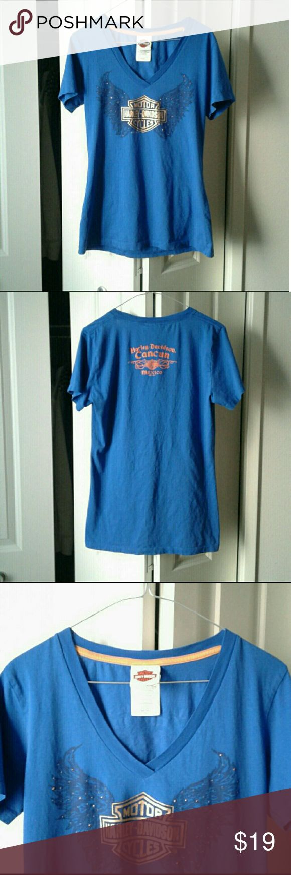 """Harley Davidson V-neck Cancun Tee V-Neck Embellished Blue HD Shirt  HD Motorcycles Graphics w/ Wings on Front - Metallic Gold  Cancun Mexico Graphics on Back - Orange   Size on tag: 2X - looks smaller, would probably fit a Medium or Large  *Possible Defect: crystals may be missing from front, or it may be the design - I didn't have this brand new so I'm not sure. Either way, it just looks like the pattern   Approx Measurements Bust 19"""" Length 27"""" Hem Width 18.5""""  Clean and Great Condition-No…"""