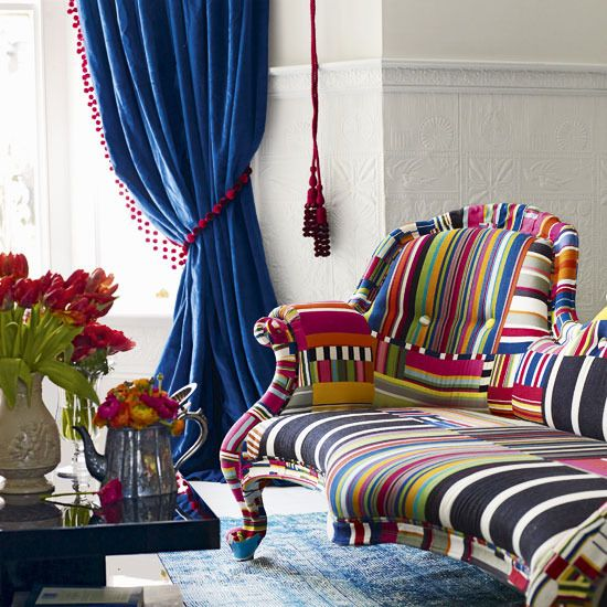 Not keen on the crazy multicoloured sofa but LOVE the red bobbles on the curtains