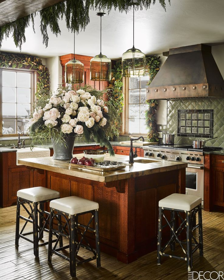 The kitchen range and hood are by Thermador, the custom island is of cherry with an oak butcher-block countertop, the stools are by Christian Liaigre, the backsplash tiles are by Pewabic Pottery, and the pendant lights (omg) are by Niche.