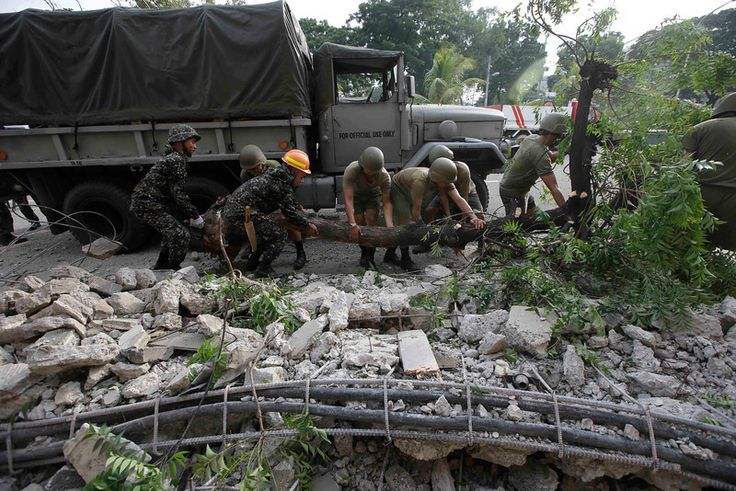 Soldiers remove the debris that fell over cars following a 7.2-magnitude earthquake that hit Cebu city in central Philippines Tuesday, Oct. ...