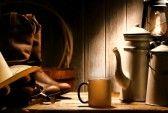 Ouest américain authentique cowboy de rodéo vitesse de travail avec le chapeau et des bottes véritable éleveur en cuir sur une table en vieux bois avec le millésime tasse et acier émaillé pot de café pour une pause dans une grange ranch antique stock photography