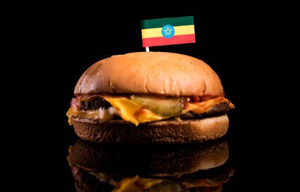ethiopian flag on top of hamburger isolated on black background