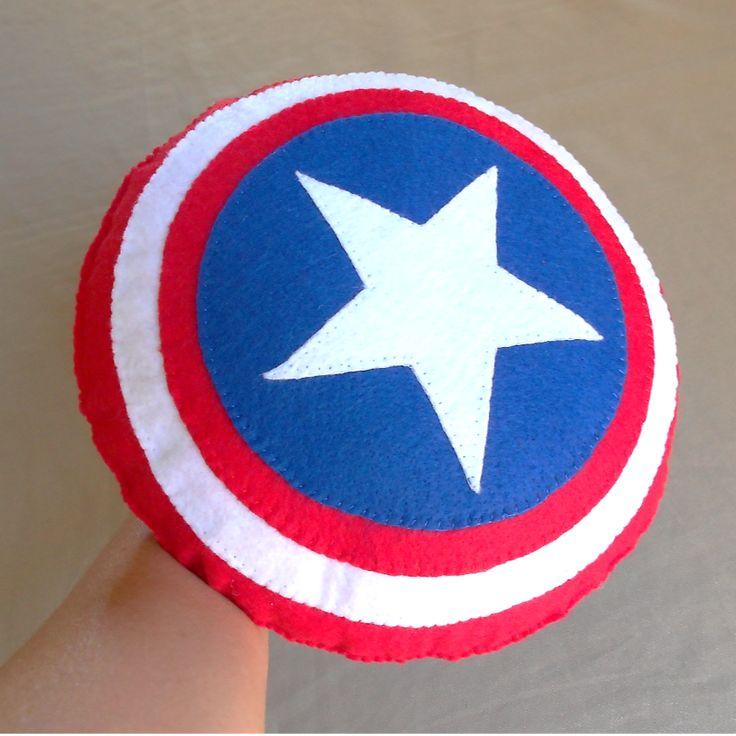 A Almofada Escudo do Capitão América em feltro mede 22 cm x 22 cm x 8 cm. É um brinquedo e também uma almofadinha. É colorido, leve, fofinho, gostoso de pegar e todo costurado. Tem alça na parte de trás para que a criança segure como um escudo.