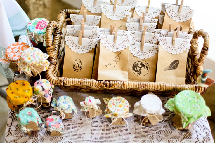 Homemade granola in jars covered with quilting squares, twine and handmade notes. Each brown paper bag was hand stamped and holds a palm oil candle.
