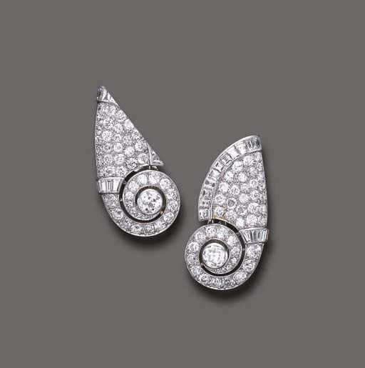 A PAIR OF DIAMOND EAR CLIPS, BY CARTIER Each designed as a pavé-set diamond scroll, enhanced by a central old European-cut diamond and baguette-cut diamond trim, mounted in platinum, circa 1933