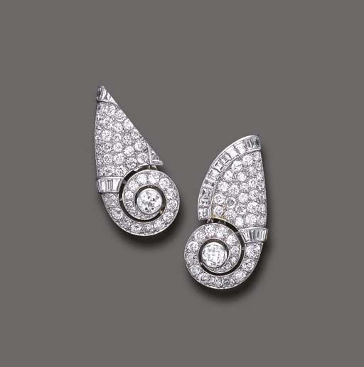 A PAIR OF DIAMOND EAR CLIPS, BY CARTIER Each designed as a pavé-set diamond scroll, enhanced by a central old European-cut diamond and baguette-cut diamond trim, mounted in platinum, circa 1933