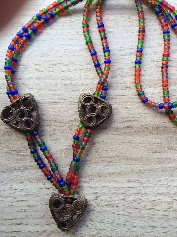 """Colar com peças de metal africanas e miçangas de vidro, foscas.  As peças de metal são triangulares e medem 2.5cm.  O colar mede 65cm.    Prazo de entrega de 2 dias.    As peças de metal são fabricadas em Ghana.  A técnica usada se chama """"fundição por cera perdida"""" e é muito antiga."""