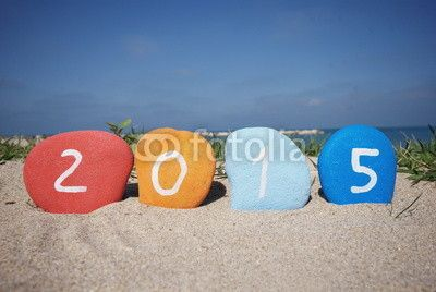 Happy 2015 with colourful stones and beach background