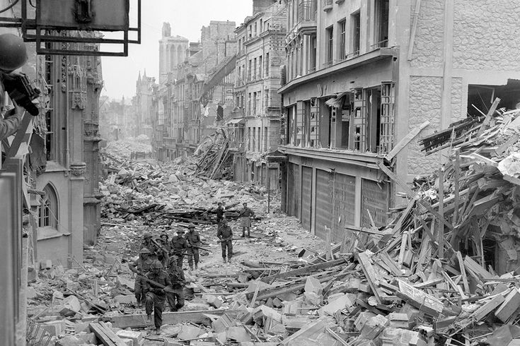 July 1944: Canadian troops patrol along the destroyed Rue Saint-Pierre after German forces were dislodged from Caen