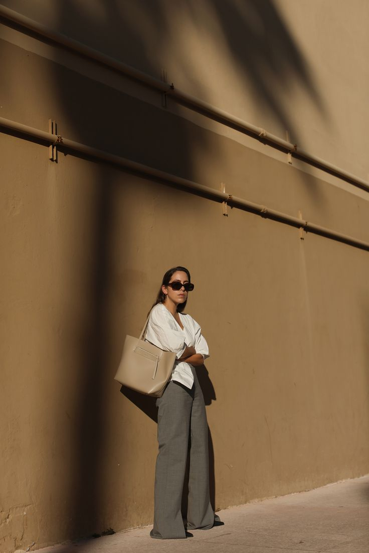 Fiona Dinkelbach from thedashingrider.com wears a white puff sleeves blouse by PETITE STUDIO NEW YORK, grey flared oversized pants by HALSTON HERITAGE, ab shopper bag by REMI & REID, black pointy boots by MANGO and ASOS sunglasses.  Location: Miami Beach, Florida - during Art Basel 2017 | The Dashing Rider | Outfit | Editorial | Summer Look | Minimalist | Minimalistic Fashion | Simple Style | Black and White | Vintage inspired | Style Blogger