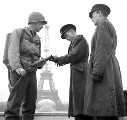 Two Polish Army officers inspect the flame-thrower of an American soldier in Allied occupied Paris while sightseeing. Paris, Île-de-France, France. 14 December 1944.   #WWII #WorldWarII #1944 #Paris #LiberationofParis #Americansoldier #Polishsoldiers #Alliedforces #Eiffeltower #AlliedoccupationofParis #France #USArmy #PolishArmy #WW2 #World War2