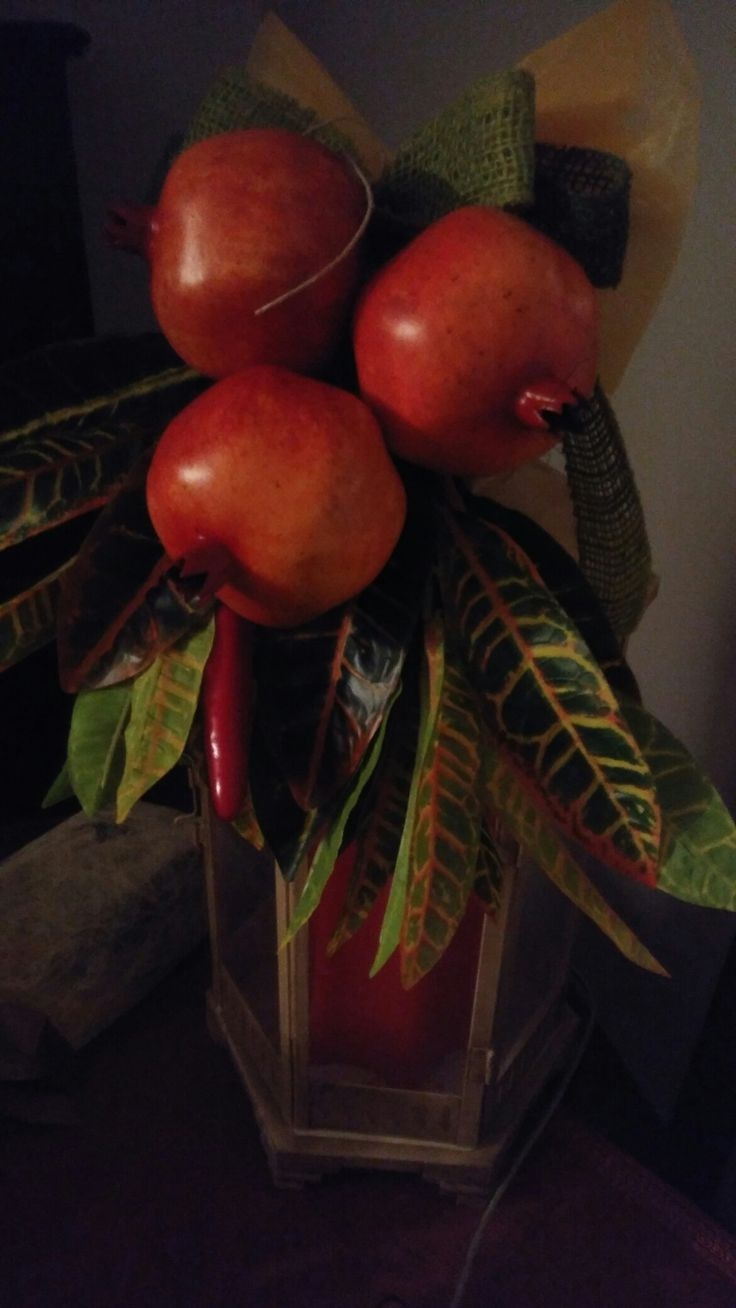 A simple lantern turned into a lovely fall deco by just adding some Styrofoam pomegranates and cheap silk foliage.
