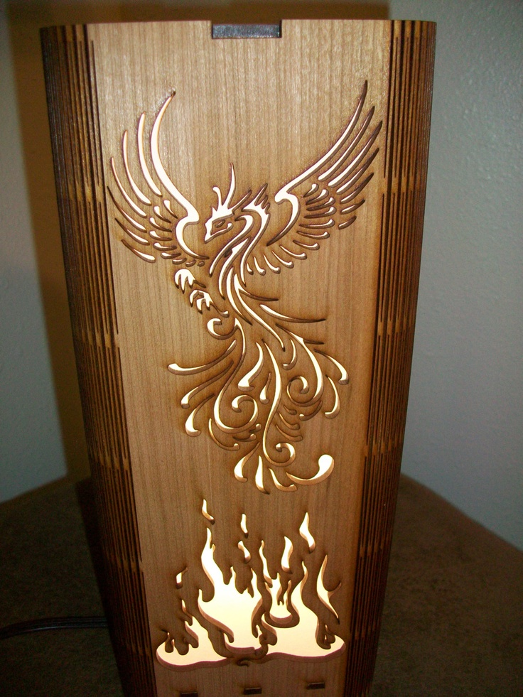 $29 Phoenix Rising Lamp - Feng Shui Lamp - Shoji Stye Lamp - Laser Cut. This one is made from a Cherry plywood material. Made from a single piece of wood...the laser cuts a unique accordian hinge that wraps to create the lamp. This is a side view, different Phoenix than on the front. Like, share, Repin!