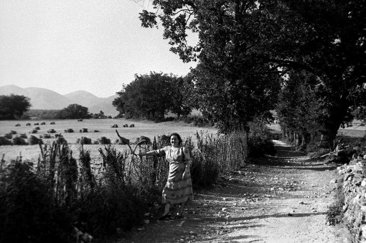San Giorgio di Cascia, anni 60. Una strada di campagna delimitat con muretti a secco, recinzioni naturali e piccole querce. Una donna che indossa gli abitii della festa, un campo appena mietuto conle cavallette del grano ben alienate. E' estate piena.