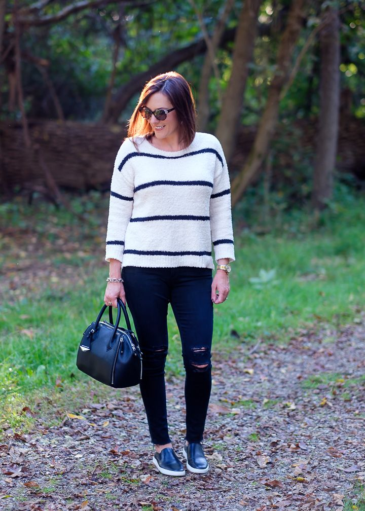 Jo-Lynne Shane wearing a striped chenille sweater with slip-on sneakers and distressed black jeans.