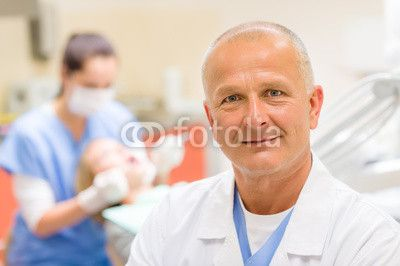Mature dentist surgeon at office portrait