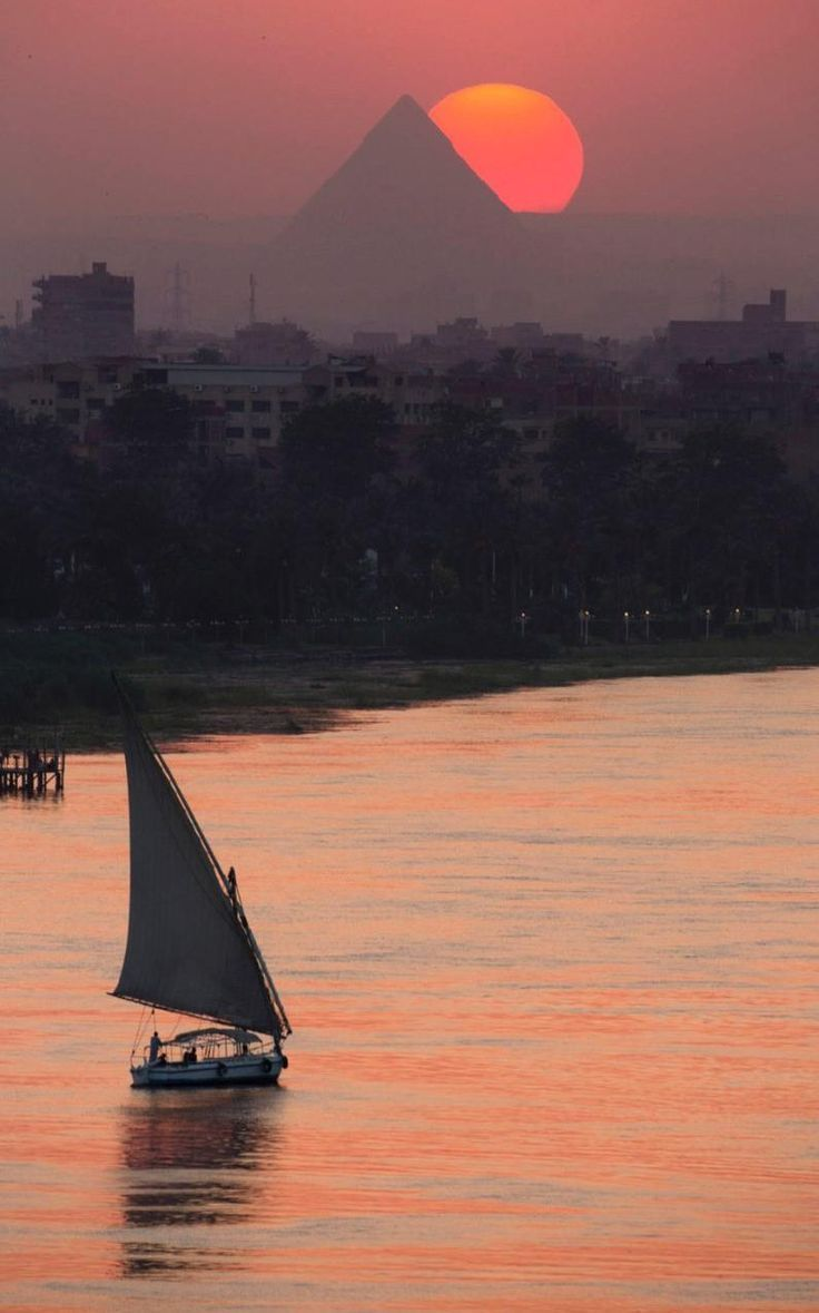 The sun sets over the historical site of the Giza Pyramids and the Nile River.