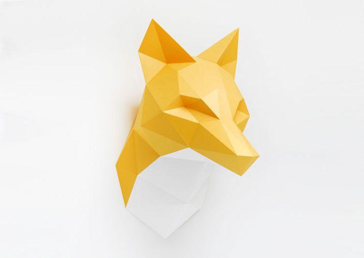 Une tête de renard blanche et orange sous forme de kit pour créer un grand trophée mural de papier. Ce kit contient 3 grandes feuilles de papier, une règle de pliage, un tube de colle et les explications d'assemblage pour réaliser soi-même son trophée renard.