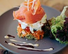 Smoked Salmon Timbale  Layers of tomato, sliced onion, avocado (when available), cream  cheese and smoked salmon trout, on salad greens, drizzled with  berry sauce