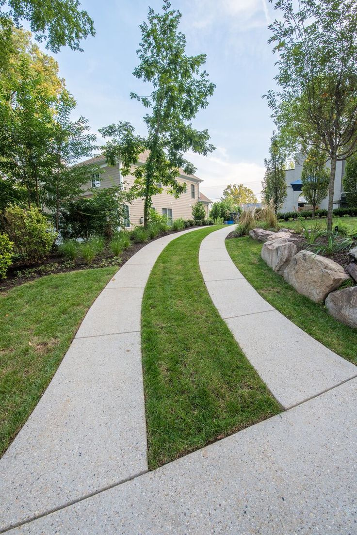 boulder plantings lining driveway of exposed aggregate wheel strips and inner grass strip