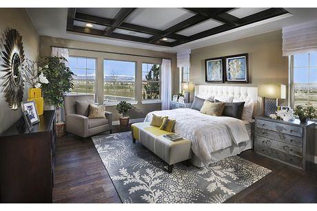 Dark beams and a rustic wood floor contrast with a gray accent rug and lighter tones. New homes in Anthem Highlands from Standard Pacific Homes. Broomfield, CO.