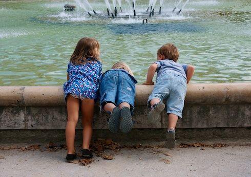 Les petits enfants jouent dans la fontaine.