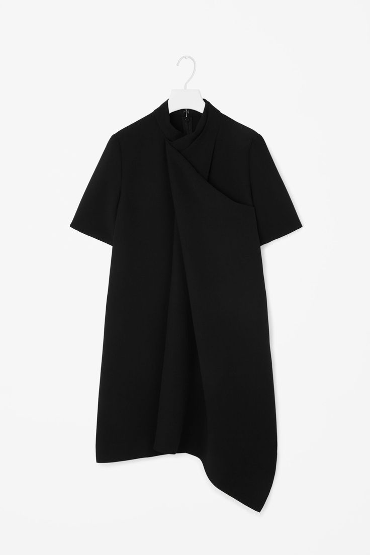 A stand-up collar and draped layer across the front, this dress is made from lightly textured fabric with a fluid movement.