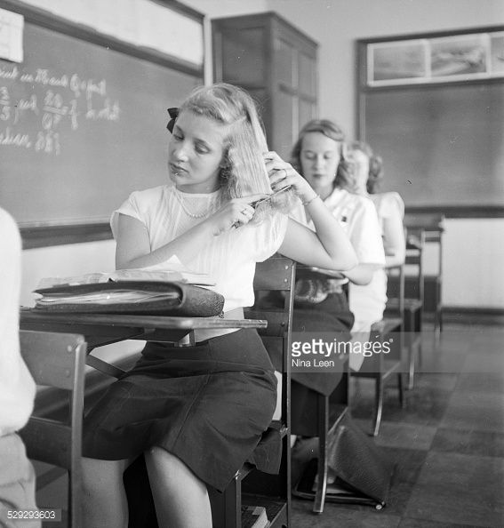 A teenage girl sitting on a chair and grooming her hair at the Will Rogers High School in Tulsa OK in 1947