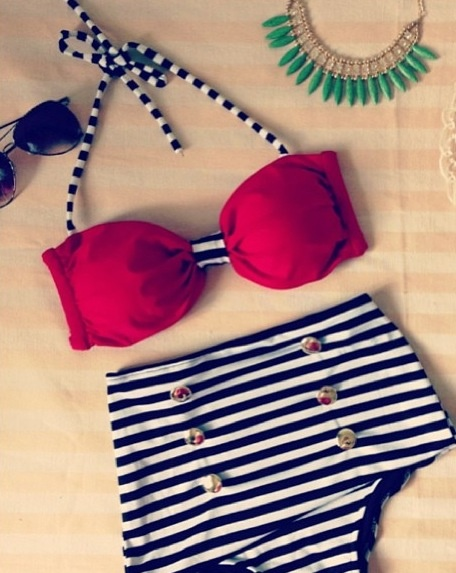 Black and white stripped,high wasted bikini with a red bikini top. Paired with a green spiked necklace and sunglasses