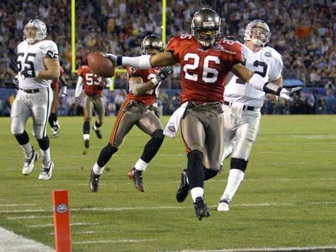 Super Bowl XXXVII (Buccaneers 48, Raiders 21): Tampa Bay's Dwight Smith races into the end zone ahead of pursuing Oakland Raiders quarterback Rich Gannon on a 44-yard interception runback for a touchdown.