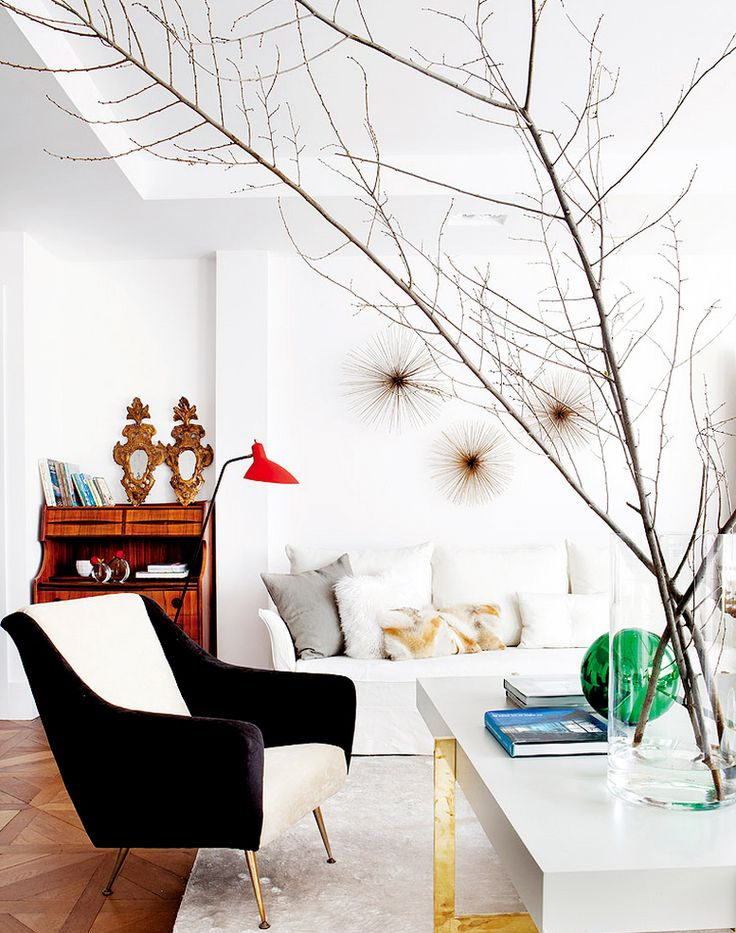 Modern and artistic living room with white sofa, black armchair, and large branches