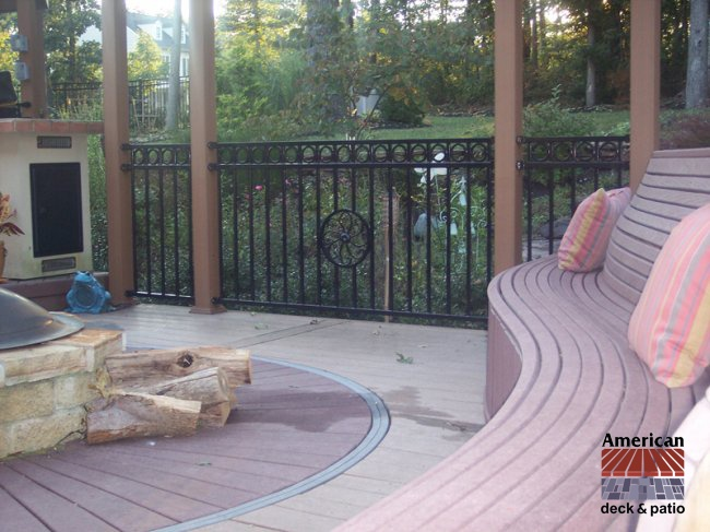 Custom Trex Curved Bench. Very intricate 4 way curved benching. Fortress Iron Rail system accents. Masonry firepit.