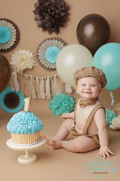 Cake smash photo session inspiration first birthday brown blue vanilla cupcake hat suspenders pom poms fans balloons bunting fabric studio lifestyle