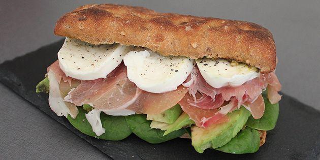 Sandwich med skinke og pesto, der smager dejligt italiensk. Det sprøde brød er fyldt med bløde stykker af frisk mozzarella og cremet avocado, der giver sandwichen perfekt fylde.