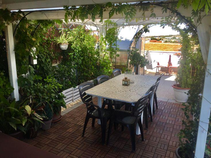 terraza con comedor, rodeada de arcos de jardín cubiertos por