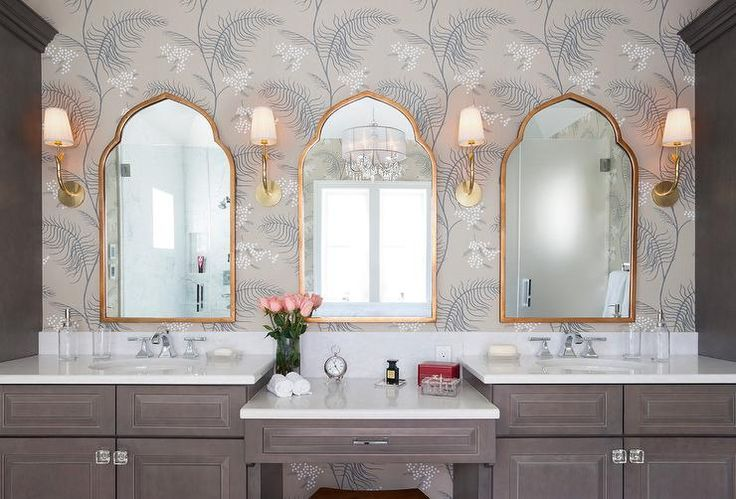 Three Mirror Image Home Pointed Arch Gold Mirrors are flanked by Hudson Valley Lighting Deering Sconces mounted to a wall accented with Cole & Son Mimosa wallpaper above a brown drop down make up vanity flanked by brown washstands adorning glass knobs and topped with white quartz countertops fitted with oval sinks and polished nickel faucets.