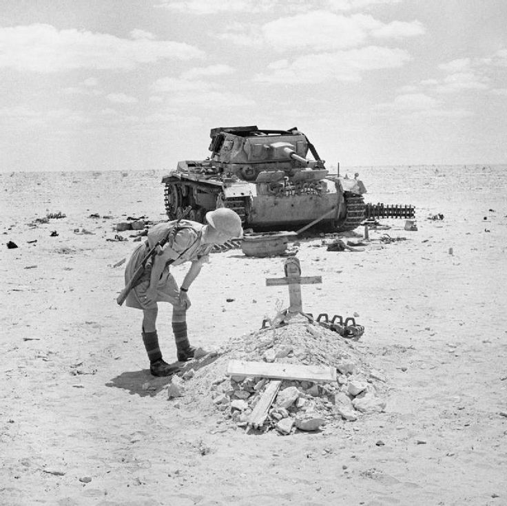 A soldiers stops to inspect the grave of a German tank crew, killed when their PzKpfw III tank, seen in the background, was knocked out in recent fighting in the Western Desert, 29 September 1942.
