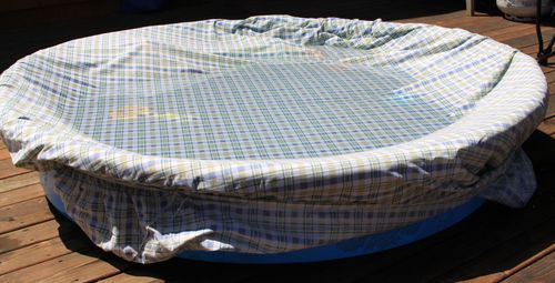 Old fitted sheet over kiddie pool to keep it clean while not in use.
