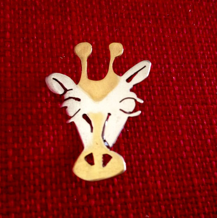 Hand made by Helen Green. Giraffe brooch cut from silver sheet and highlighted with gold plate.