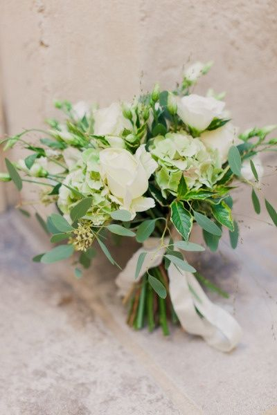 Small naturally shaped bouquets of seasonal foliages, white wax flower and blush spray roses wrapped in emerald green ribbon with the stems showing