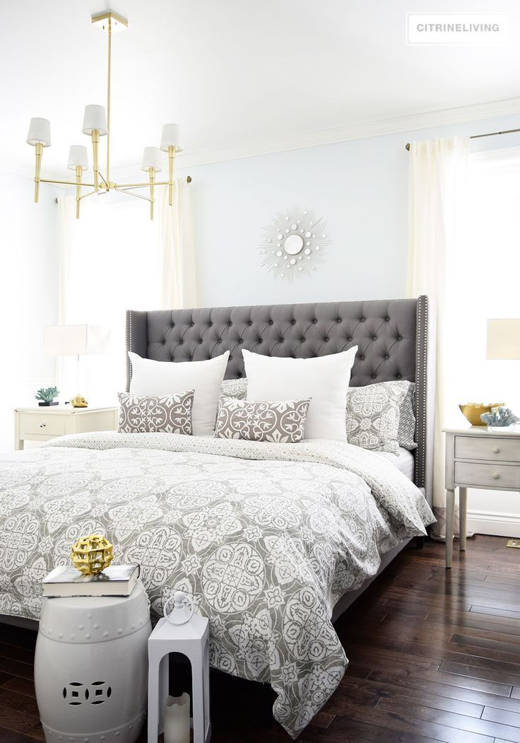 A brass chandelier and accents add modern sophistication to this elegant  bedroom.