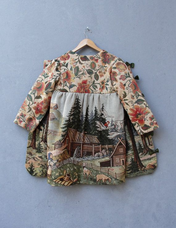 We have made this lovely coat with a vintage (1940s) gobelin tapestry very finely woven with lots of details showing scenery of the Russian fairy tale Baba Yaga, in English know as The Magic Swan Geese with the magic Geese flying away with the boy, whereas his sister runs after them to get her brother back. Other details such as a watermill, trees, the hut of Baba Yaga, goats, houses fences, birds and many more little details of the fairy tale are shown on the entire coat. The arms and top…